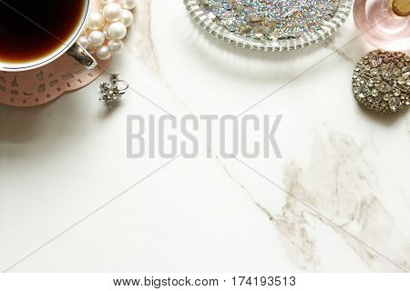 Chic and elegant styled vanity with coffee, pearls, diamonds, perfume, and glitter. Open space against white marble.