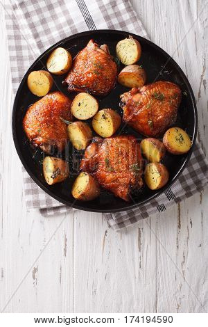 Roast Chicken Thighs And Baby Potatoes With Maple Syrup Closeup. Vertical Top View