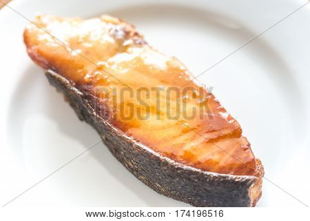 Roasted fish steak on the white plate
