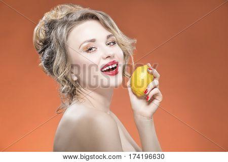 Sexy Fruit Series. Smiling Happy Naked Caucasian Blond Girl With Lemon Fruit. Against Orange Background. Horizontal Image