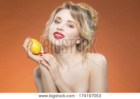 Sexy Fruit Series. Naked Caucasian Blond Girl Posing With Yellow Lemon Fruit. Against Orange Background. Horizontal Image