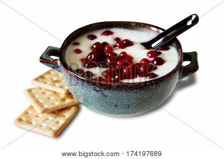 Sweet semolina with berries and crackers for Breakfast.  Porridge with cowberry in a ceramic bowl. Isolated on white background with shadow. Horizontal location.