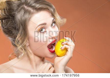 Sexy Fruit Series. Closeup Portrait of Happy Naked Caucasian Blond Girl Biting Yellow Lemon Fruit. Posing Against Orange Background. Horizontal Image