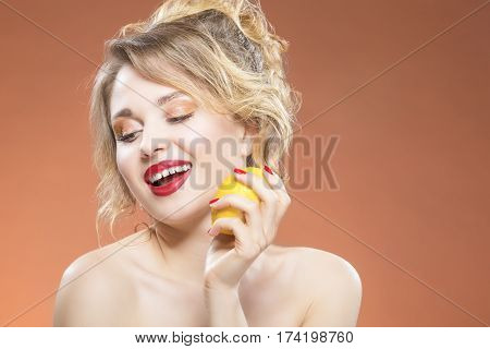Sexy Fruit Series. Portrait of Sensual Sexy Caucasian Blond Girl Biting Yellow Lemon Fruit. Posing Against Orange Background. Horizontal Image Orientation
