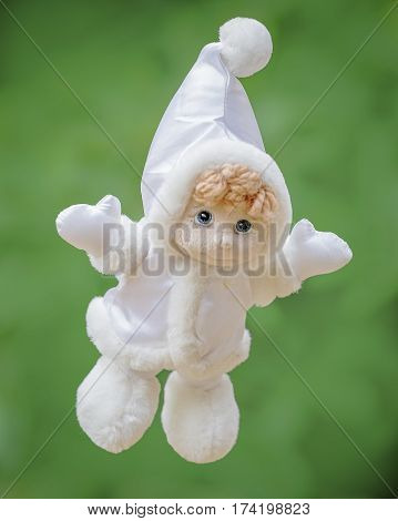 Plush white doll on a green background .