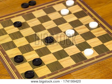 checker board with checkers on wooden background