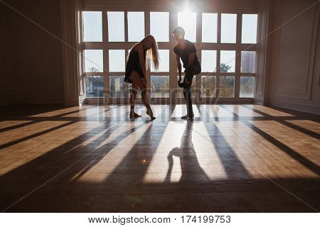A young boy and girl with long blond hair standing in front of the window. Dancers during a workout. Problems and difficulties in relations. The difficult situation in life. Conceptual photography