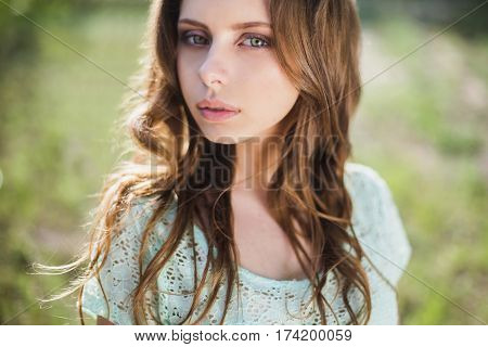 Fine art photo. Art beauty portrait of a very pretty young girl. Art doll appearance. Woman with brown hair in a turquoise dress on nature. Long hair. Natural light. Art portrait. Art concept