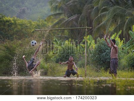 Children play soccer in the river .