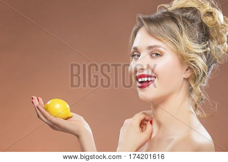 Portrait of Sexy Alluring Tanned Caucasian Woman Posing with Lemon in Hand. Against Orange Background. Horizontal Image Orientation