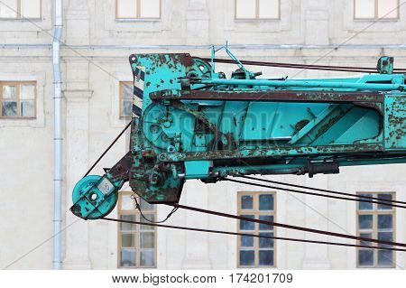 part of old working turquoise crane truck for construction on a background Palace