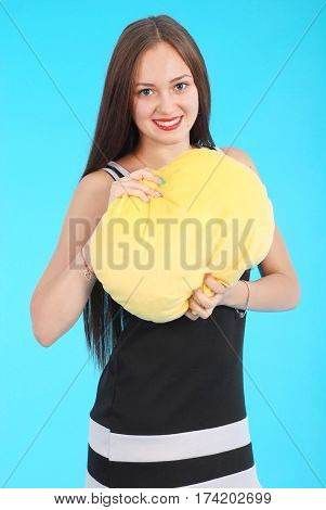 Cheerful young girl is holding a smiley face pillow are standing against the blue background