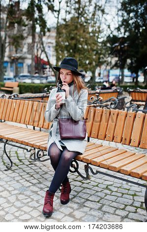 Young Model Girl In A Gray Coat And Black Hat With Leather Handbag On Shoulders Sitting On Bench And