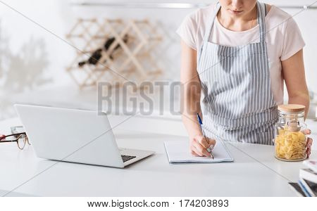 Noting the essentials. Focused dedicated pretty woman using her laptop finding a pasta recipe while making notes in her notebook