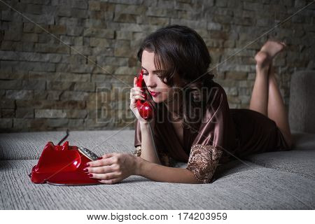 Girl PinUp with brunette hair and retro make-up with red lips in a bathrobe on a dark background. The girl lies on a bed. Vintage image. Woman talking on the phone. Disk phone. Feeling sadness.