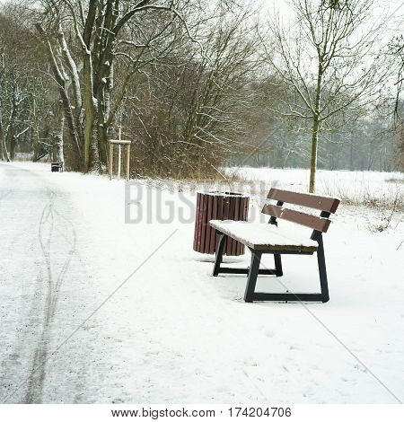 Abandoned bench in the city park of Magdeburg in winter