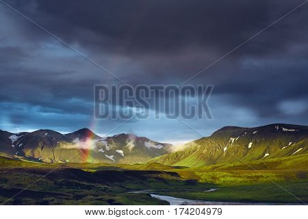 Travel to Iceland. Beautiful sunset in camping near Alftavatn lake. Icelandic landscape with mountains, sky and clouds. Trekking in national park Landmannalaugar. Rainy Evening with big rainbow.