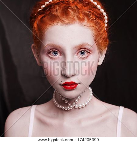 Woman with long red hair pinned on her head a necklace of beads on a black background. Red-haired girl with red lips pale skin blue eyes a bright unusual appearance in a white dress