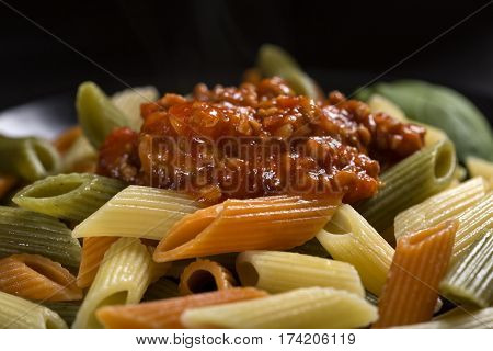 Colored penne pasta with ragu sauce or bolognese pasta on plate