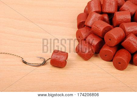 Fishing bait with hook and red pre-drilled halibut pellets for carp fishing isolated on wood background with soft shadow