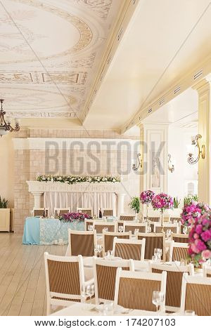 Celebrations hall, elegant banquet hall interior. Tables set for meal. Bright and colors checkered ceiling in colorful modern interior with chandelier. Elements of the decor