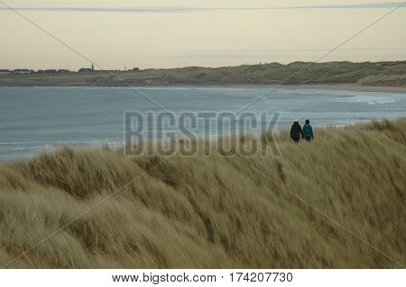 Two ladies walking on the ridge of sand dunes in Fraserburgh, Scotland