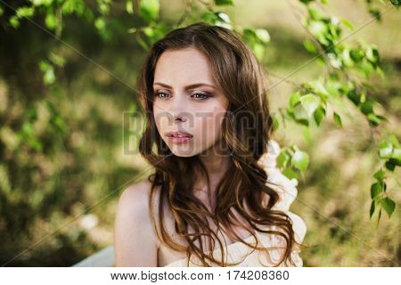 Beauty portrait of a very pretty young girl. Doll Beauty appearance. Beauty woman with brown hair in a pink wedding dress on nature. Long hair beauty style. Natural light. Beauty portrait