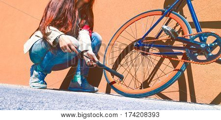 Young woman inflating bike wheel in a sunny day outdoors - Girl fixing bicycle tire outside at summer time coming on orange urban wall background - Concept about two wheeler commuter lifestyle