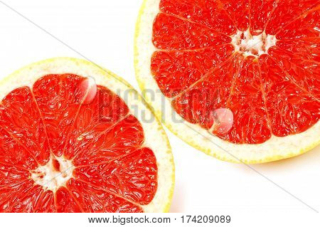 Slices of red juicy grapefruit with water drops isolated on white