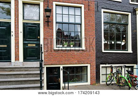 Fragment of a traditional redbrick house in Amsterdam with large clean windows and bicycles nearby