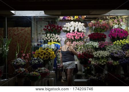 KIEV UKRAINE - AUGUST 10 2015: Florist (middle aged woman) working on her flowers in an underground of Independence - Maidan Square