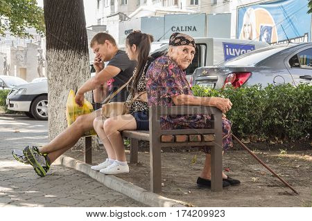 CHISINAU MOLDOVA - AUGUST 11 2015: Old woman sitting on a bench next to a young couple the woman being pregnant