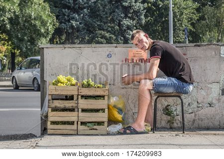 CHISINAU MOLDOVA - AUGUST 11 2015: Young man sitting on a stool selling grapes in the capital city of Moldova. Grape and fruits more generally are one of the main exports of the country