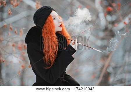 A  retro woman with red hair in a black retro coat on background of a winter forest with a mouthpiece in hand. Red-haired retro girl with bright appearance with a retro turban on her head with a cigarette. Smoking aesthetics. Retro model