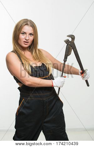 Nice sexy woman mechanic holding wrench. isolated on white background