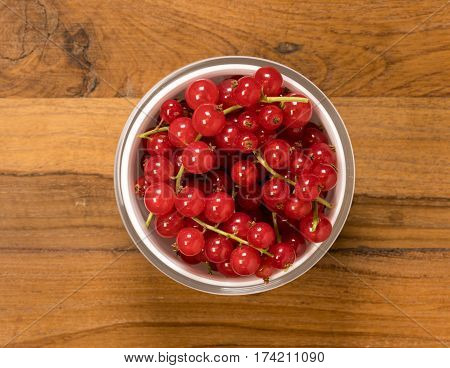 Aerial or top view of a white glass bowl of organic redcurrant or red currant fruit  sitting on old wood table surface