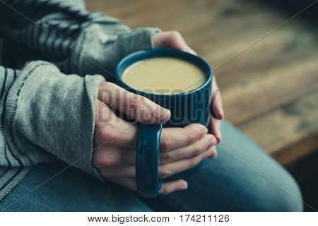 Woman get warming up with a cup of hot coffee