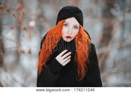 A woman with red hair in a black coat with fur on a background of winter forest. Red-haired girl with pale skin and blue eyes with a bright unusual appearance with a turban on her head in winter. Women's winter style