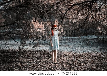 Slavery. Very cute young girl with a blindfold red ribbon lost in forest. Doll appearance. Woman with brown hair in a turquoise dress on nature lost. Long hair. Natural light. Model posing on the nature lost. Kidnapping