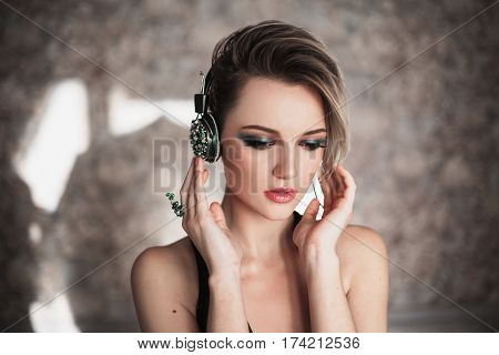 Music concept. Lovely girl with tanned skin and white hair listening to music on headphones. Female beauty portrait of a beautiful makeup listen music. Enjoying good music.