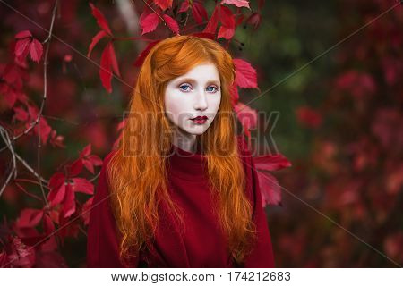 Woman face with red straight hair in a red coat on a bright autumn background. Red-haired girl face with pale skin and blue eyes and a bright unusual appearance with a ring on finger and red nails. Street style
