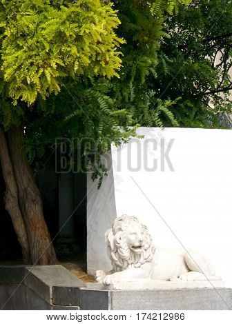 sculpture of a white lion on a background of white walls and green trees