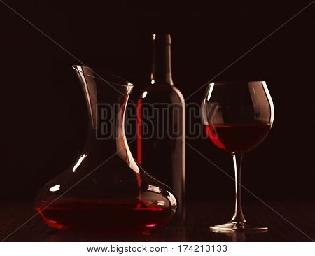 Decanter with wine, glass and bottle in darkness