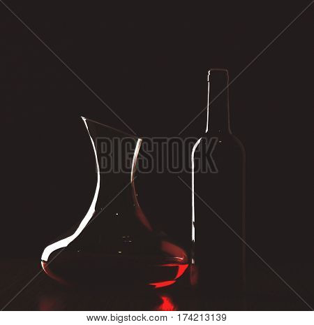 Decanter with red wine and bottle in darkness