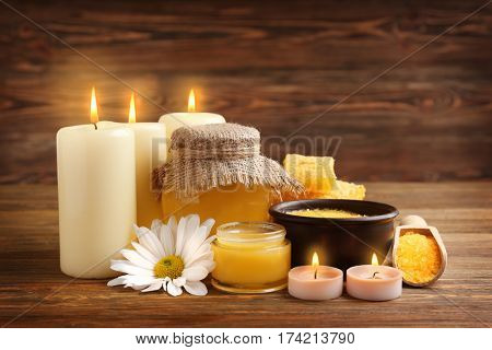Spa concept. Composition of honey, sea salt and natural wax candles on wooden background