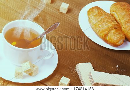 Early morning: sunlit scene of cup of hot coffee with steam, croissant and wafer on a rustic wooden table. Healthy breakfast.