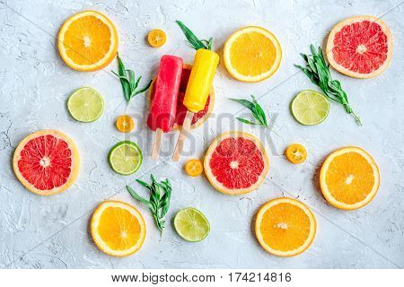 homemade ice-cream with sliced oranges and lime on stone table background top view pattern