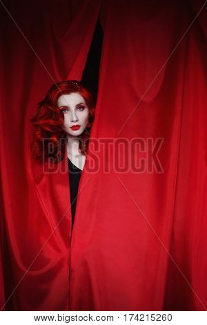 A woman in theater with red curly hair in a black dress looking out of a red fabric. Red-haired girl with pale skin a thin waist blue eyes a bright unusual appearance red lips in theater. Retro makeup. Theatre actress