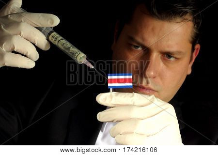 Young Businessman Gives A Financial Injection To Costa Rican Flag Isolated On Black Background