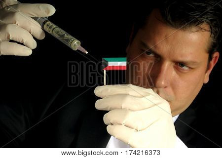 Young Businessman Gives A Financial Injection To Kuwaiti Flag Isolated On Black Background